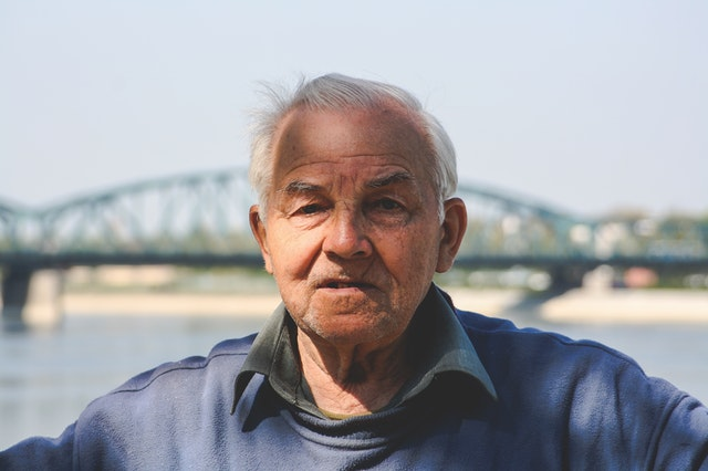 Old man in front of a bridge