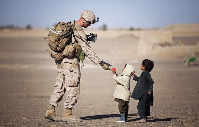 Soldier giving apple to kids