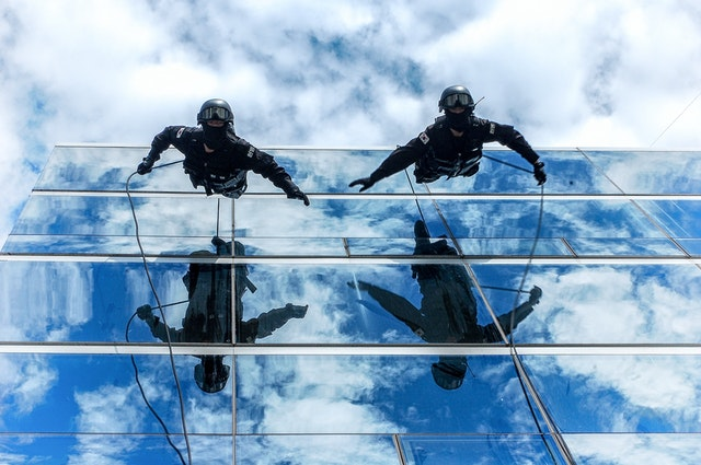 2 men scaling down a building with ropes, illustrating the money concept of risk
